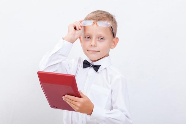 Ritratto del ragazzo teenager con il calcolatore su fondo bianco