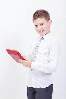 Ritratto del ragazzo teenager con il calcolatore sulla parete bianca