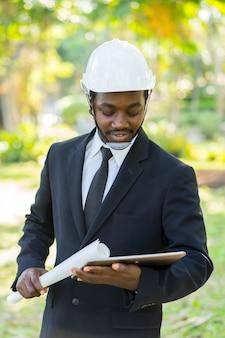 Ritratto del responsabile afroamericano dell'ingegnere industriale con verde naturale.