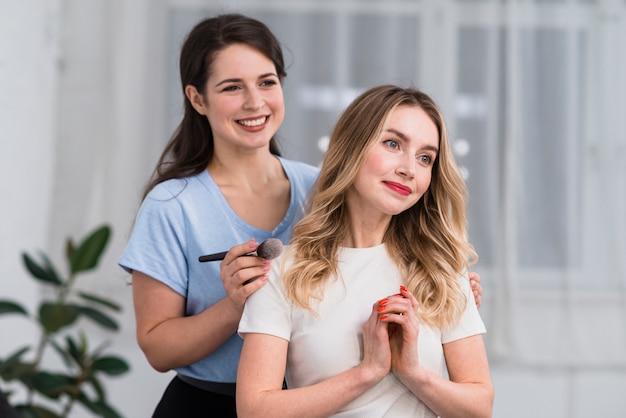 Ritratto del truccatore che usando spazzola e donna bionda felice