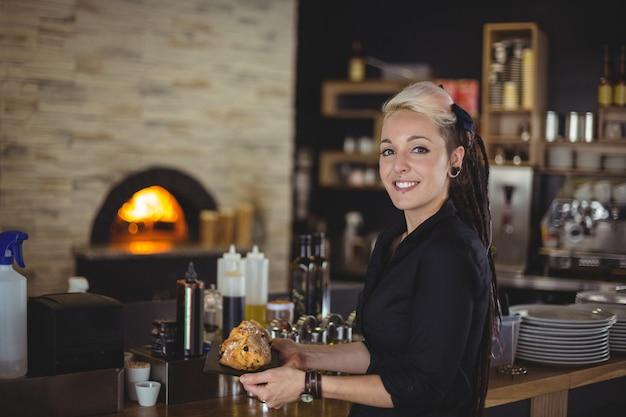 Ritratto del vassoio della tenuta della cameriera di bar di muffin al contatore