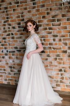 Ritratto del vestito da sposa d'uso dalla ragazza dai capelli rossi contro uno studio bianco.