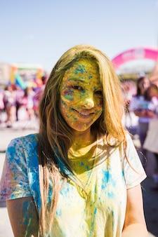Ritratto del volto di una giovane donna coperto con polvere di holi guardando la fotocamera