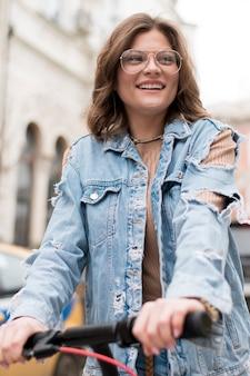 Ritratto dell'adolescente alla moda che guida motorino elettrico