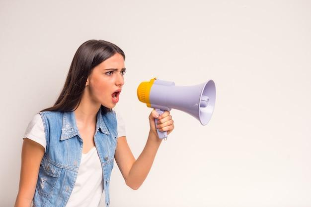 Ritratto dell'adolescente allegro della ragazza, gridante in un megafono.