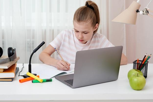 Ritratto dell'adolescente che impara online con le cuffie e il computer portatile che prendono le note in un taccuino che si siede al suo scrittorio a casa che fa i compiti