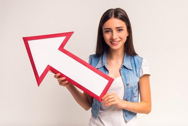 Ritratto dell'adolescente emozionale della ragazza con la freccia di carta.