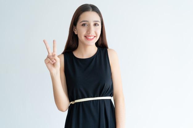 Ritratto dell'adolescente felice che mostra gesto di vittoria