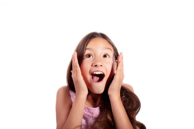 Ritratto dell'adolescente sorpreso, emozionante, colpito che osserva in su isolato su bianco