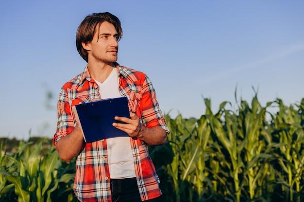Ritratto dell'agronomo sorridente che sta in un campo di mais che prende il controllo del rendimento
