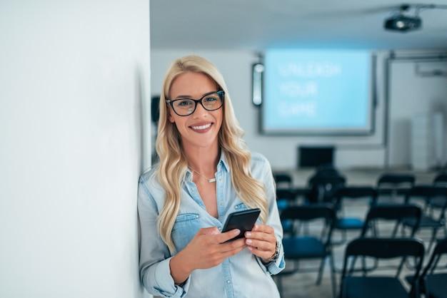 Ritratto dell'altoparlante femminile che utilizza telefono nella sala per conferenze vuota. guardando la fotocamera