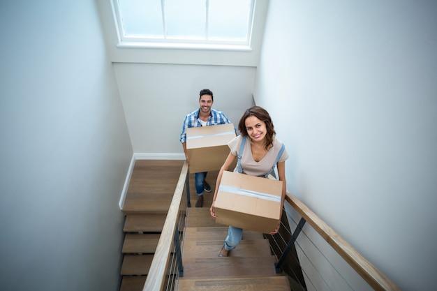 Ritratto dell'angolo alto delle scatole di cartone sorridenti della tenuta delle coppie mentre salendo i punti