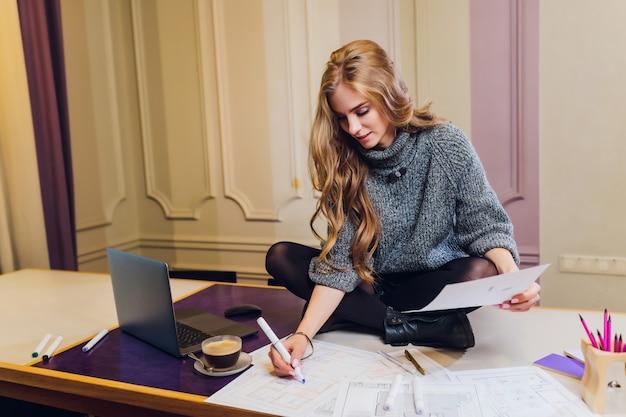 Ritratto dell'architetto arredatore femminile sorridente che si siede alla scrivania.