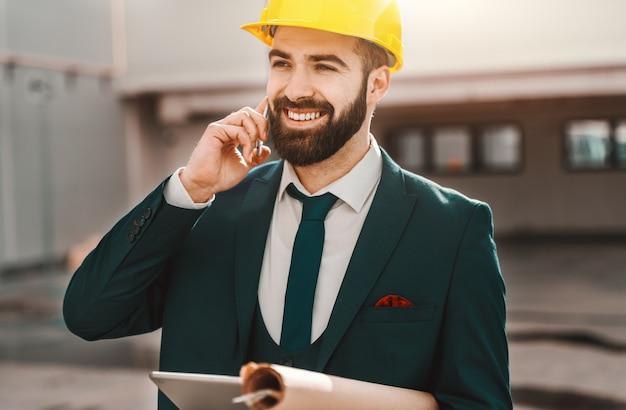 Ritratto dell'architetto barbuto nell'usura convenzionale che parla sul telefono e che tiene progetto e compressa mentre stando sul cantiere.