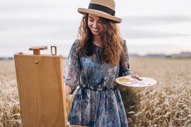 Ritratto dell'artista femminile sorridente con capelli ricci in cappello. la ragazza disegna un'immagine di un paesaggio in un campo di grano