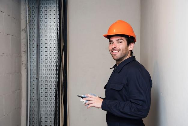 Ritratto dell'elettricista maschio sorridente che esamina macchina fotografica