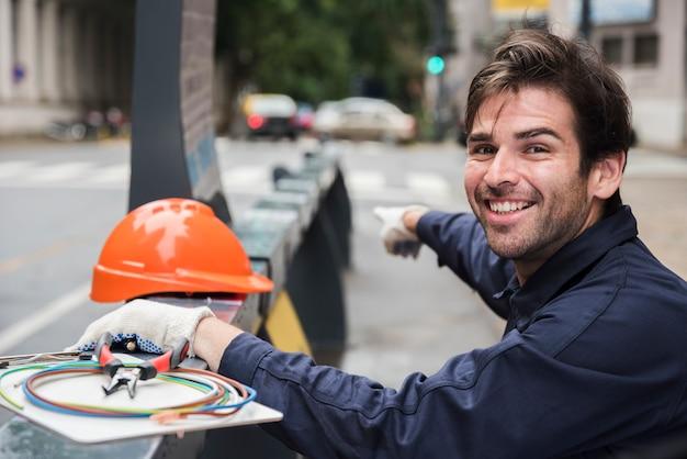 Ritratto dell'elettricista maschio sorridente che indica con il cappello duro e l'attrezzatura sulla via