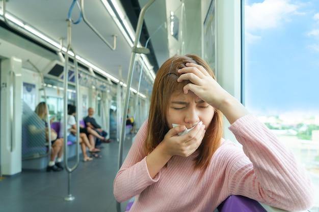 Ritratto dell'emicrania o del malumore della giovane donna mentre prendendo lo sky train.