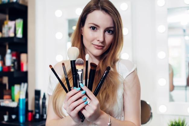 Ritratto dell'estetista femminile che tiene un insieme delle spazzole di trucco nel salone di bellezza