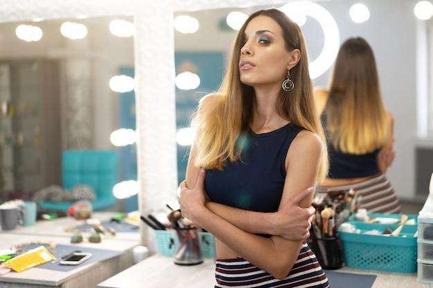 Ritratto dell'estetista femminile grazioso che sta posante nel posto di lavoro nel salone di bellezza e dei capelli