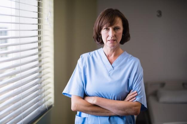 Ritratto dell'infermiere che sta con le armi attraversate