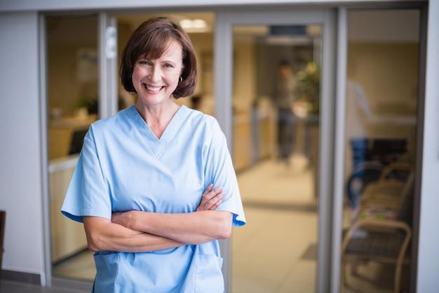 Ritratto dell'infermiere sorridente che sta con le armi attraversate