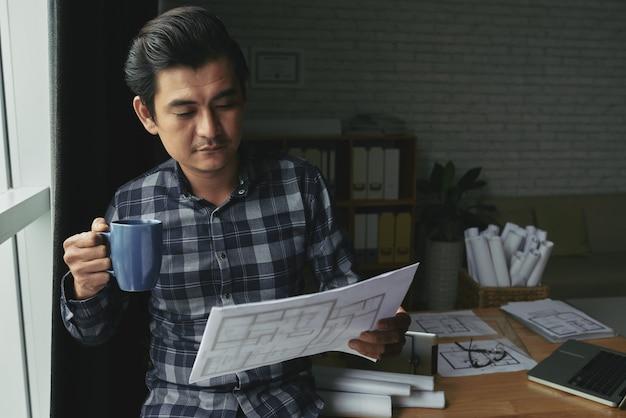 Ritratto dell'ingegnere asiatico che tiene una tazza di tè e che esamina il progetto di progettazione