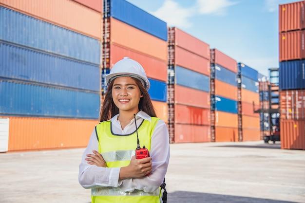 Ritratto dell'ingegnere logistico con il supporto del casco di sicurezza in cantiere navale nel giorno soleggiato