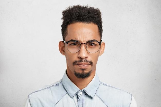 Ritratto dell'interno del modello maschio sconvolto scontento scontento con pettinatura alla moda, baffi, barba, indossa occhiali rotondi