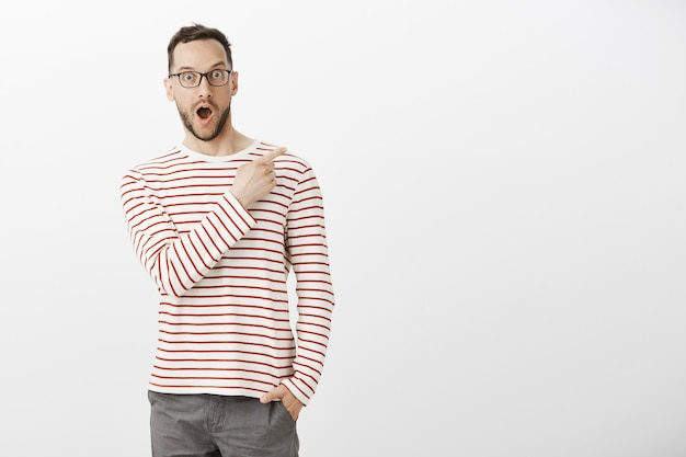 Ritratto dell'interno dell'uomo bello impressionato contento in occhiali, che punta nell'angolo in alto a destra, lasciando cadere la mascella dalle emozioni positive