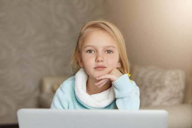 Ritratto dell'interno della bambina europea sveglia adorabile con capelli biondi