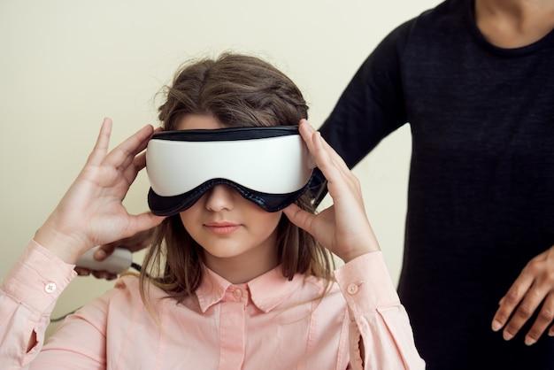 Ritratto dell'interno della donna caucasica rilassata e sicura sull'appuntamento con optometrista che si siede nel suo ufficio mentre collaudando vista con screener di visione digitale, indossandolo sugli occhi