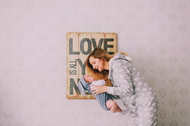 Ritratto dell'interno della ragazza hapy nella tenuta del pijama, abbracciante il suo neonato vicino alla parete con il piatto decorativo. la mamma si prende cura del suo bambino. concetto di maternità. l'amore è tutto ciò di cui hai bisogno
