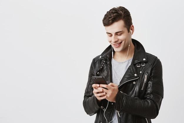 Ritratto dell'interno di bel ragazzo caucasico in giacca di pelle di tendenza che tiene il telefono cellulare, messaggistica con i suoi amici, raccontando loro del suo viaggio all'estero con un piacevole sorriso