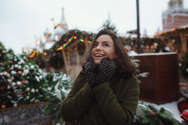 Ritratto dell'interno di bella ragazza in rivestimento rosso di inverno che sta soffiando neve sulla fiera di natale