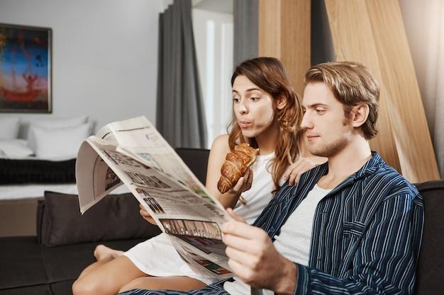 Ritratto dell'interno di coppia carina innamorata, leggendo il giornale in appartamento, seduto sul divano, indossando il pigiama. la ragazza legge la pagina dell'oroscopo e mangia il cornetto mentre il ragazzo controlla le notizie di affari