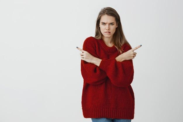 Ritratto dell'interno di donna attraente travagliata confusa in elegante maglione sciolto, labbro mordace, aggrottando le sopracciglia e indicando in diverse direzioni, interrogato e scontento, avendo problemi a scegliere
