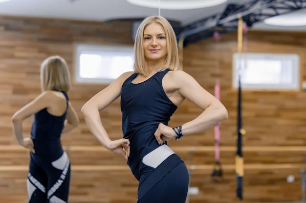 Ritratto dell'istruttore personale della donna bionda adulta di forma fisica