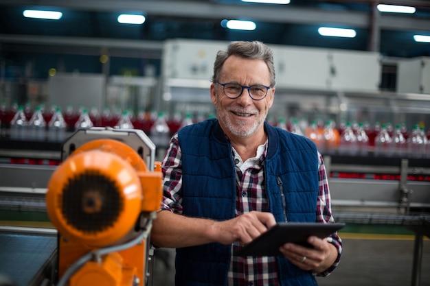 Ritratto dell'operaio sorridente che sta con una compressa digitale nella fabbrica