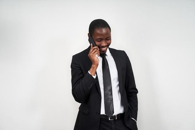 Ritratto dell'uomo africano che sorride mentre parlando al telefono con la parete grigia
