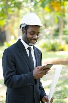 Ritratto dell'uomo africano di affari di sorriso che gioca smartphone con la natura.