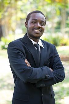 Ritratto dell'uomo africano di affari di sorriso sulla natura.