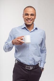 Ritratto dell'uomo africano felice che mangia tazza di caffè