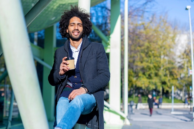 Ritratto dell'uomo afro bello allegro nella posa di abbigliamento casual
