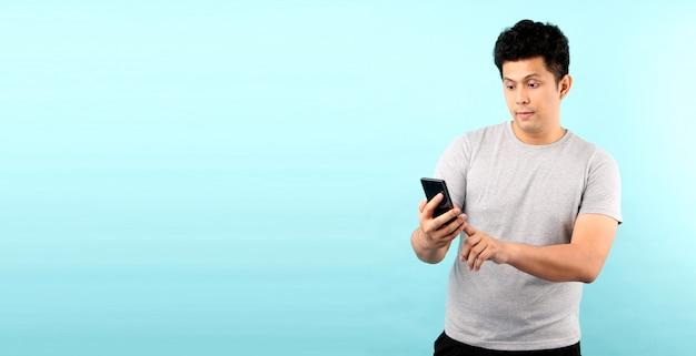 Ritratto dell'uomo asiatico bello che è scossa e sorpreso dopo la lettura del messaggio dallo smarrtphone, isolato sulla parete blu.