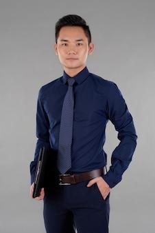 Ritratto dell'uomo asiatico bello una mano che tiene una lavagna per appunti un'altra in tasca che esamina macchina fotografica