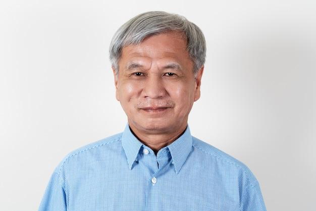Ritratto dell'uomo asiatico senior attraente che sorride e che esamina macchina fotografica in studio