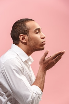 Ritratto dell'uomo attraente con il bacio isolato sopra il rosa