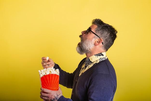 Ritratto dell'uomo attraente con la barba e gli occhiali da sole che mangiano popcorn dal profilo alla macchina fotografica su fondo giallo.