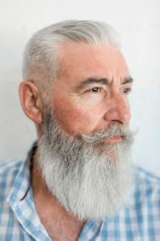 Ritratto dell'uomo barbuto serio invecchiato in camicia in studio